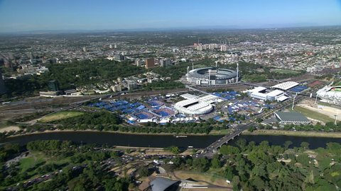 A wide sweeping aerial shot of Melbourne City, Victoria, Australia, from a helicopter, across the green botanical gardens and Yarra River towards the tennis stadiums and MCG sports ground.