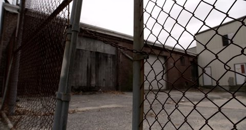 Locked fence at old abandoned industrial building. Camera dollies towards chain and tilts up.
