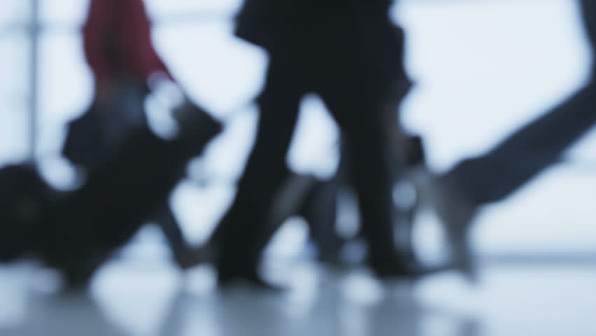People walking in Airport transit terminal with luggage baggage going on travel or business trip. Busy modern life and transport concept with closeup of feet and and legs out of focus and blurry.
