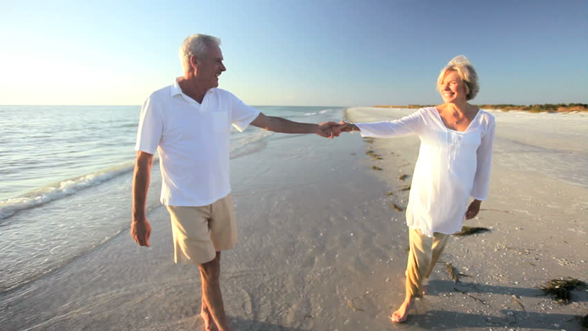 Carefree senior couple romantically dancing together on a beach at sunset