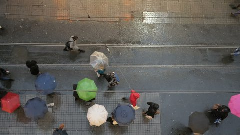 Crowd of people walking with umbrellas on Istiklal Street on a rainy day, Beyoglu, Istanbul, Turkey.