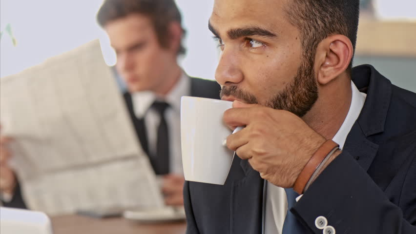 Medium shot of middle eastern business man enjoying his coffee break, ofter his meeting and thinking wile drinking his coffee in cafe.