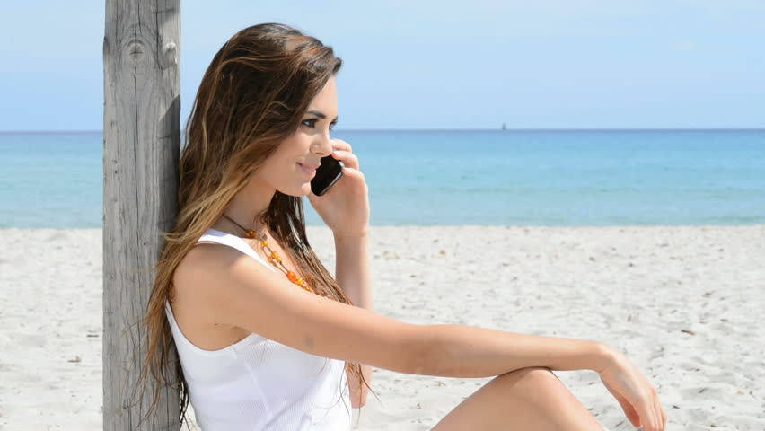 64eb643273 Happy Young Woman At Beach Talking On Cellphone. Smiling girl sitting on  the beach at phone. Beautiful positive woman talking on phone at seaside in  ...