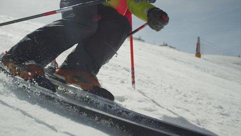SLOW MOTION CLOSEUP: Slalom skiing between the gates