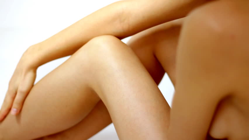 Woman gently touching her leg, isolated on white