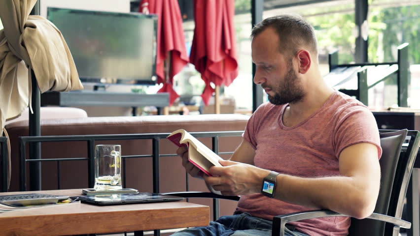 Young man reading book sitting in cafe in city