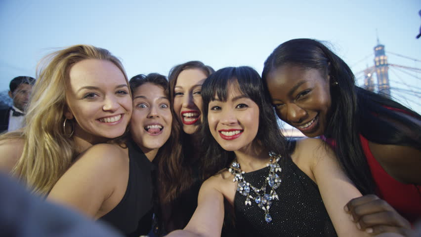 4K Attractive fun loving female friends pose to take a selfie at party