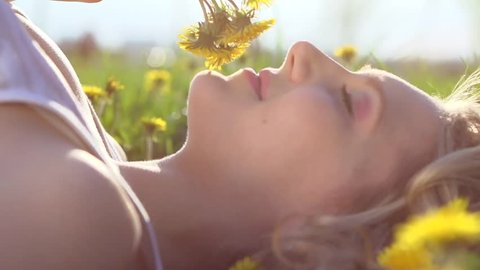 Beauty Girl lying on dandelions meadow and smelling flowers. Beautiful Spring Young Woman Outdoors Enjoying Nature. Healthy Girl in Green Grass. Allergy free. Slow motion 240 fps. 1080p