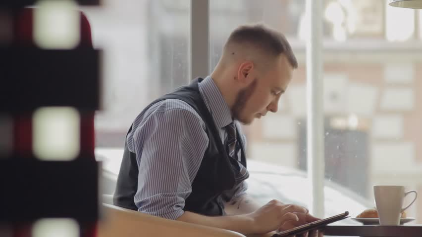 Young man drinking coffee in cafe and using tablet computer | Shutterstock HD Video #9751373