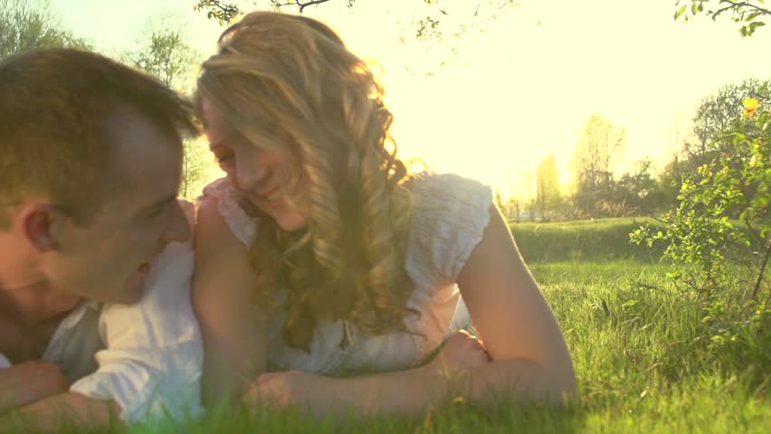Happy Smiling Couple Relaxing on Green Grass. Park.Young Family Lying on Grass Outdoors. Healthcare, love concept. Slow motion 240 fps, high speed camera shot. Full HD 1080p #9768914
