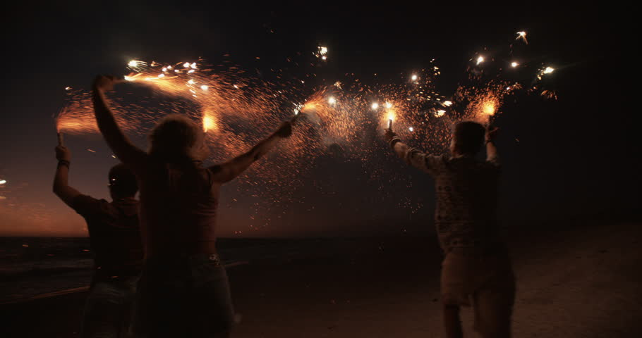 Rearview of friends running together on a beach holding sparkling fireworks in Slow Motion | Shutterstock Video #9774770