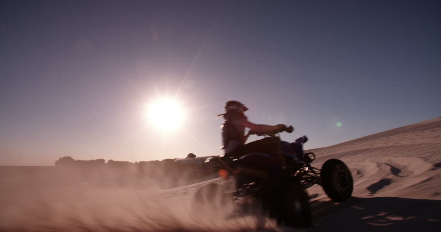 Competitive quad biker kicking up a plume of sand while racing over a sand dune