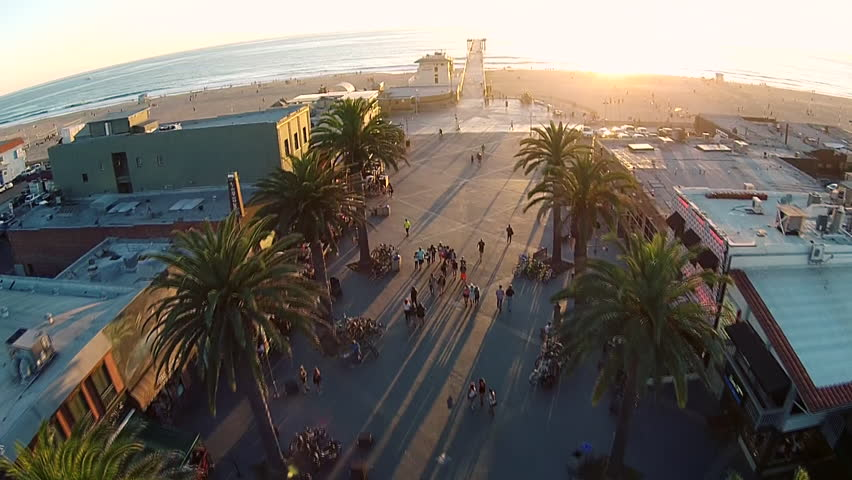 Aerial video of the Hermosa Beach Pier, California. Scenic view overlooking the ocean and revealing palm trees and the tourist area, as the camera moves backwards