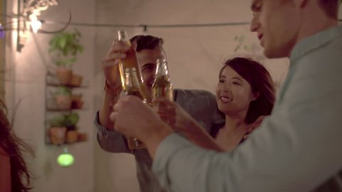 Smiling mixed race couple holding beers and enjoying a casual party at their friends' home