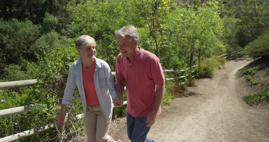 Happy mature couple walking on trail