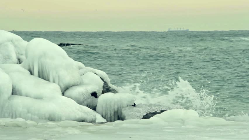 Foaming wave is breaking on the ice coverd stone. Cargo container ship sailing. | Shutterstock HD Video #9826184