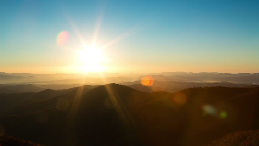 Timelapse of the sun rising over mountains with bokeh sun flare | Shutterstock HD Video #9828854