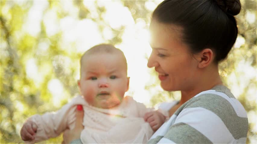 Beautiful young mother playing with her newborn baby in a lush garden, laughing | Shutterstock HD Video #9858794