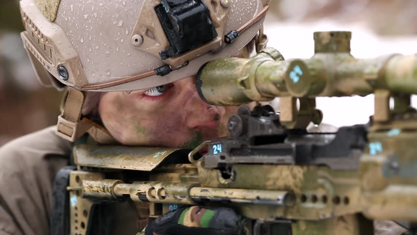 armed man in camouflage with aiming sniper rifle