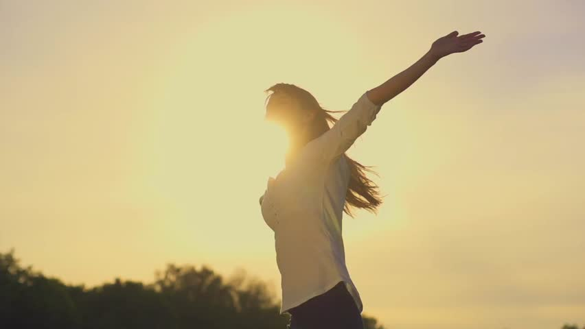 Attractive young woman silhouette dancing outdoors on a sunset with sun shining bright behind her on a horizon. Slow motion, shot at 240 fps. #9875954