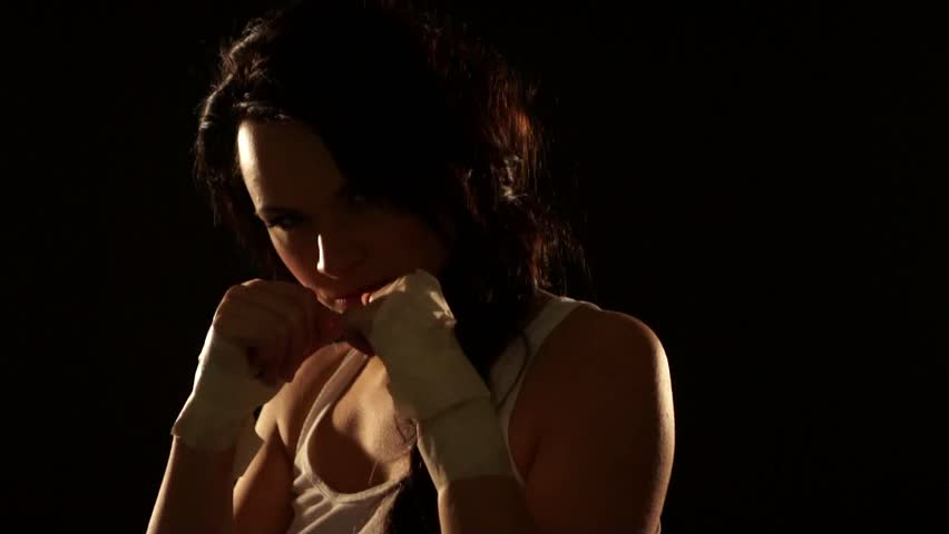 Young sexy woman boxing over dark background