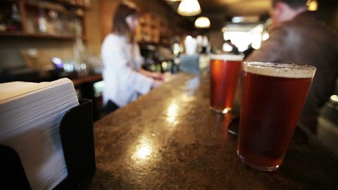 Video footage of a London bar scene with tight and shallow focus on the foreground beer on the bar while a background scene of barmaid and customers falls into the heavy blur.