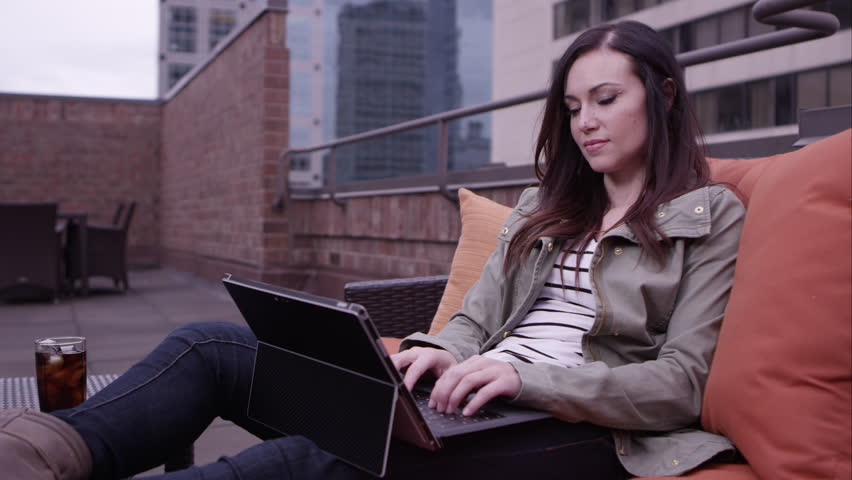 Woman relaxing on roof top adjusting laptop and typing. | Shutterstock HD Video #9888494