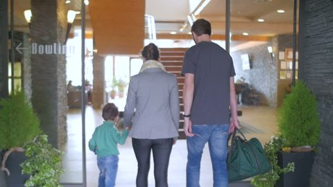 Slow motion of a family entering a hotel reception rear