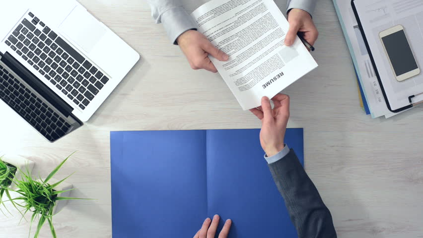 Businessman checking a candidate's resume during a job interview and shaking hands after hiring him, hands top view
