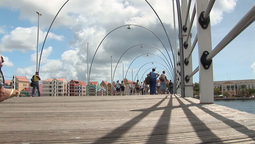 Unrecognizable people walking on pontoonbridge in Willemstad, Curacao, Netherlands Antilles.