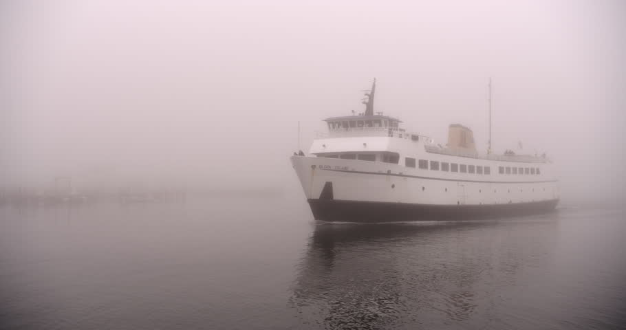 Block Island car ferry leaving port at Galilee Narragansett, Rhode Island, New England, USA on a foggy day with a small fishing village visible in the mist.