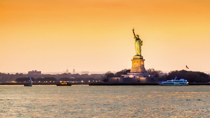 Timelapse with the Statue of Liberty in transition from sunset to night observed from Brooklyn, New York City. Boats criss-cross the Hudson River. | Shutterstock HD Video #9993692